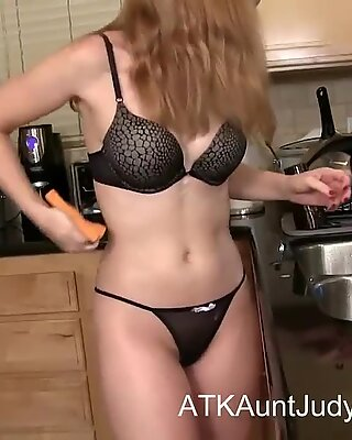 Blonde mature Heidi washes the dishes
