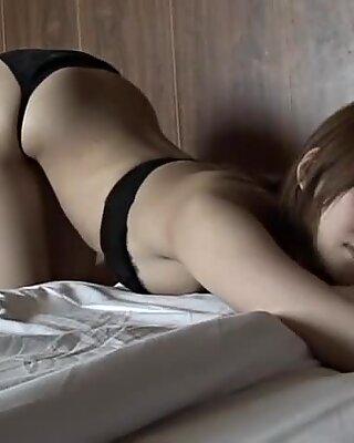 Accrocheur asiatique séductrice se trouve sur le lit en bikini
